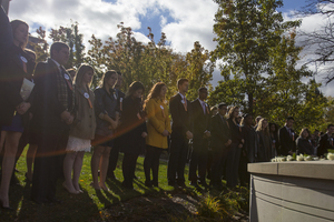The 2015-16 Remembrance Scholars stand in front of the Wall of Remembrance during last year's Rose Laying Ceremony, which concludes the Remembrance Week events.