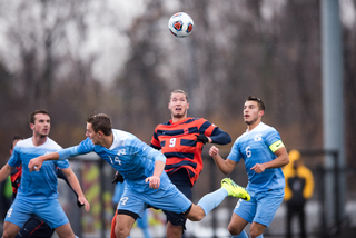 Syracuse Johannes Pieles goes up for a header in the middle of three Tar Heels defenders.