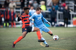 UNC's Jeremy Kelly prepares to kick the ball as Syracuse's Mo Adams applies pressure.