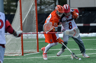 Mariano tries to fight off the Red Storm's goalie Daniel Costa to scoop up a ground ball.