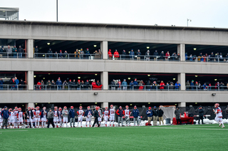 Fans crowded into a parking lot across the field to watch the game, despite it being 12 degrees at the start.