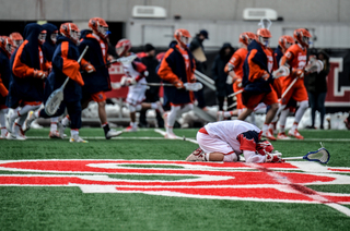 SJU's TJ Marron stays in disappointment as Syracuse celebrates the win.